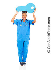young african nurse holding a large key - attractive young...