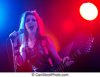 Rock star singing on stage - Young rock star singing with...