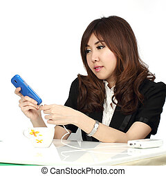 businesswoman charging her mobile phone - Young attractive...