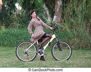 Pin-up girl poising on a bike - a beautiful pin-up woman,...