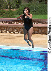 Girl jumping in swimming pool holding her nose