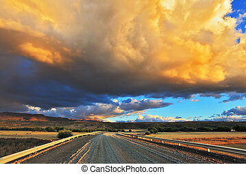 Storm over the Pampas In the steppe runs a gravel road The...