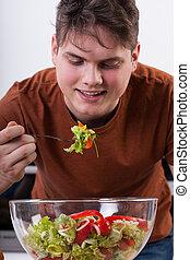 Happy man eating salad