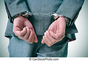 handcuffed man - a man wearing a suit with his wrists...