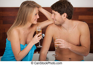 Bathroom champagne toast - A couple proposing a toast with...
