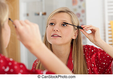 Blonde applying mascara - A pretty blonde woman applying...