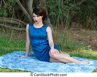 pin up girl - Beautiful young woman sitting on a blanket at...