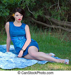 pin-up woman - Beautiful young woman sitting on a blanket at...