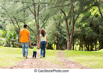 family holding hands walking in forest - rear view of young...