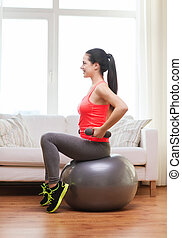 smiling girl exercising with fitness ball - fitness, home...