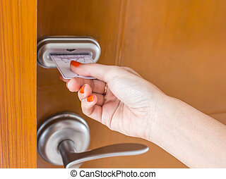 womans hand inserting key card in an electronic lock