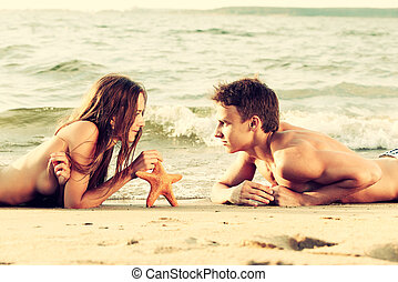 couple at the beach - Colorized vintage outdoor portrait of...