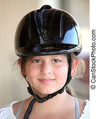 jockey  - The face of a little girl in jockey  hat.