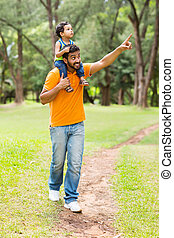 caring young indian father and son walking outdoors in...