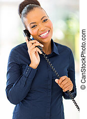 african office worker talking on telephone - happy african...