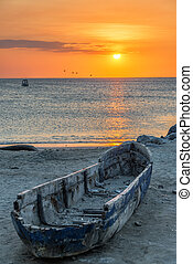 Canoe and Sunset - Old damaged wooden canoe with a beautiful...