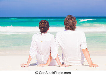 back view of happy young honeymoon couple in white clothes sitting on beach