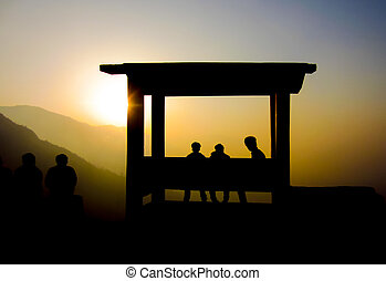 Silhouette of people watching sunset