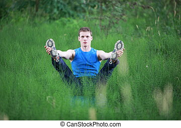man  practicing yoga on meadow