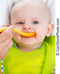 mom feeding baby with a spoon
