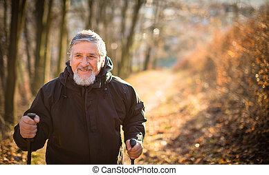 Senior man nordic walking, enjoying the outdoors, the fresh...