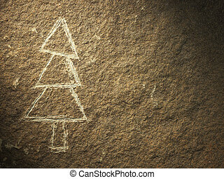 rock painting of christmas tree on stone textured surface