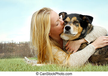 Young Woman Kissing German Shepherd Dog Outside - a young...