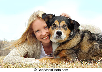 Smiling Woman Hugging German Shepherd Dog - a happy young...