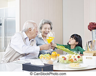 happy asian family - granddaughter toasting with grandma and...