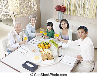 happy asian family - three-generation family having meal at...