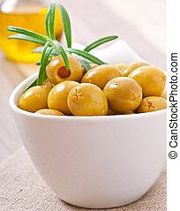 Green olive in bowl.