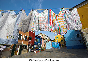 Burano street - Multicolored buildings and laundry drying on...