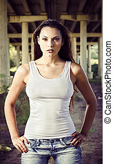 Beautiful young woman in shirt and jeans stands under bridge