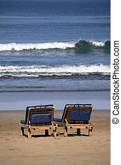 Bali beach - Inviting wooden chairs on a Bali beach
