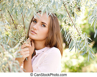 Sensual portrait of a beautiful young woman in the summer garden