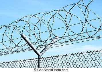 Barbed wire against blue sky.