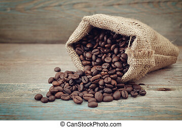 Sack of coffee beans on wooden background closeup