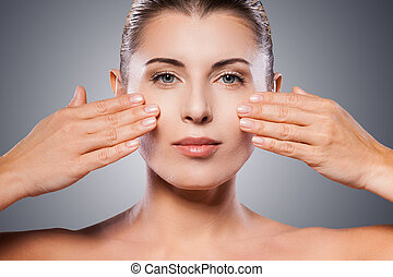 Face care Beautiful mature woman keeping eyes closed and...