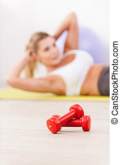 Training her abs. Mature woman exercising on mat with dumbbells laying on foreground