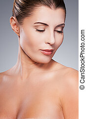 Fresh and beautiful. Portrait of shirtless mature woman looking at her shoulder while standing against grey background