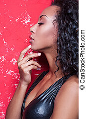 Glamour fashion model. Beautiful young Afro-American woman with make up and hairstyle posing against red background