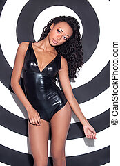 Glamour fashion model. Beautiful young Afro-American woman with make up and hairstyle posing against stripped background