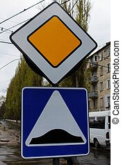 Main road and Speed bump signs - A close-up photo of Main...