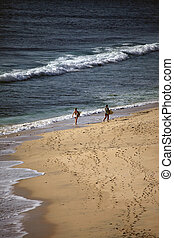 Dreamland - Two girls with boards for surfing at coast of...