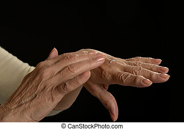 Older woman applying cream on hands closeup on black...