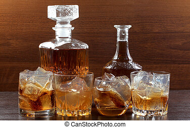 Whiskey in bar - Glass jars with whiskey and ice on wood...