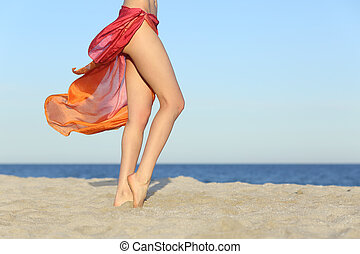 Standing woman legs posing on the beach wearing a pareo with...
