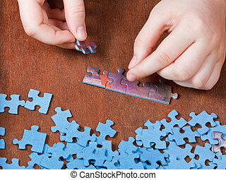 fitting of jigsaw puzzles on wooden table