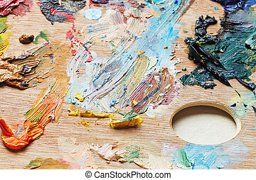 oil paint brush strokes on wooden artistic palette close up