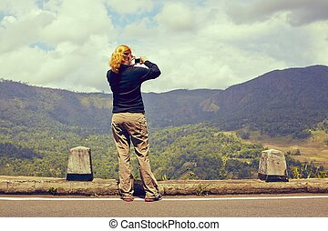 Pictures from mountains - Young woman is taking pictures of...